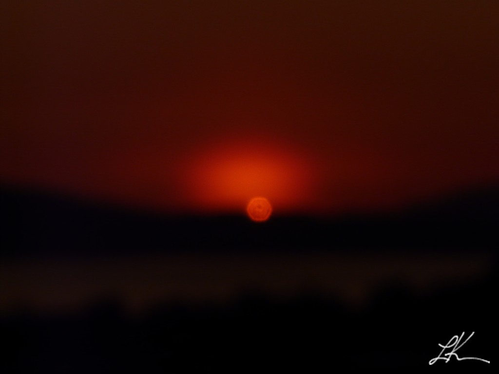 Photo: Red glow above setting sun.