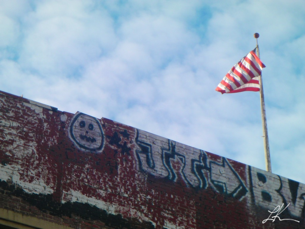 Photo: American flag above graffiti-covered wall.